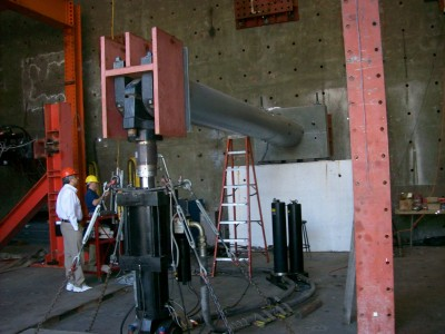 UCSD's test setup used a hydraulic actuator, with the sign structure specimen bases bolted to a concrete retaining wall.