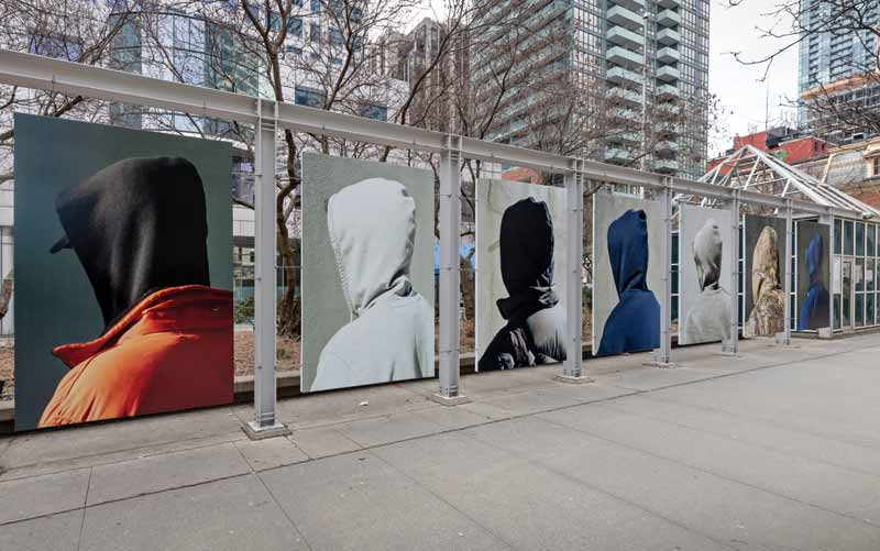Four By Eight used beam clamps to install a series of 13 grey steel structures, displayed along King Street West near Metro Hall.