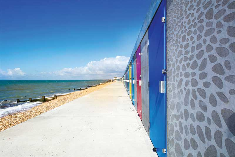 The graphic concrete used to replace 119 storm-damaged beach huts in Hampshire, England's Milford-on-Sea, includes a whimsical pattern in keeping with the beach, as well as illustrations of actual local vistas.