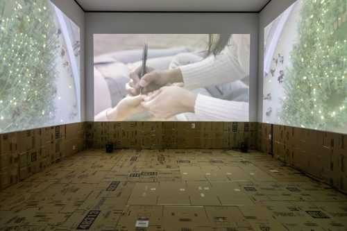 Lumapit Sa Akin, Paraiso (Come to Me, Paradise), 2016, three-channel high-definition (HD) video with colour and sound (25:44 min), cardboard, dimensions variable. Installation view of the Sobey Art Award Exhibition, Art Gallery of Alberta, Edmonton, 2019. © Stephanie Comilang, courtesy the artist.