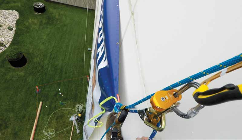A banner being hauled up with ropes using mechanical advantage and specialty equipment.