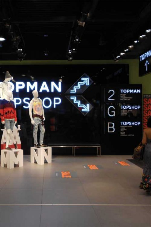 Fashion retailer Topshop has employed a large toolkit of visual elements to support wayfinding including a hierarchy of illuminated elements such as neon icon signs, directories, and product displays.
